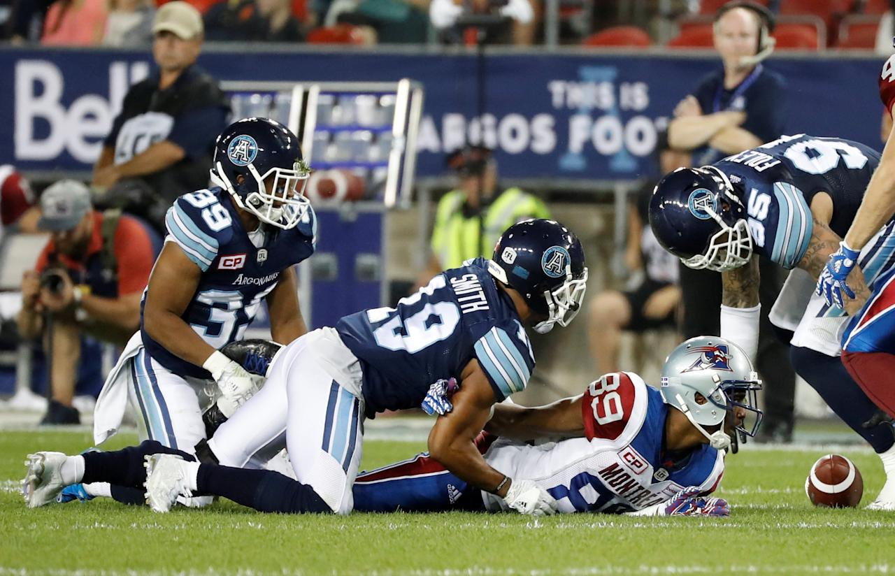 Montreal Alouettes Duron Carter fumbles the ball against Toronto Argonauts Devin Smith (19), Matt Black (39), and Ricky Foley (95) during the second half of their CFL game in Toronto, July 25, 2016.     REUTERS/Mark Blinch