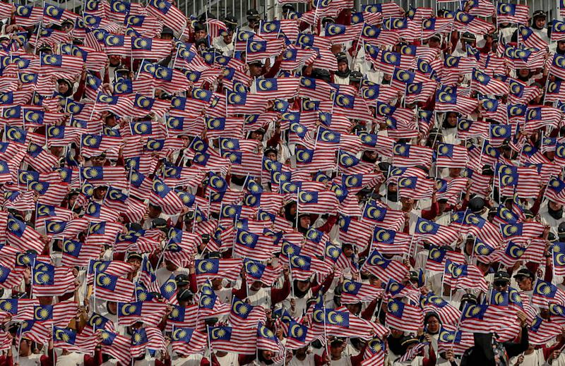 Participants wave the Malaysian flag during a National Day rehearsal in Putrajaya August 29, 2019. — Picture by Firdaus Latif