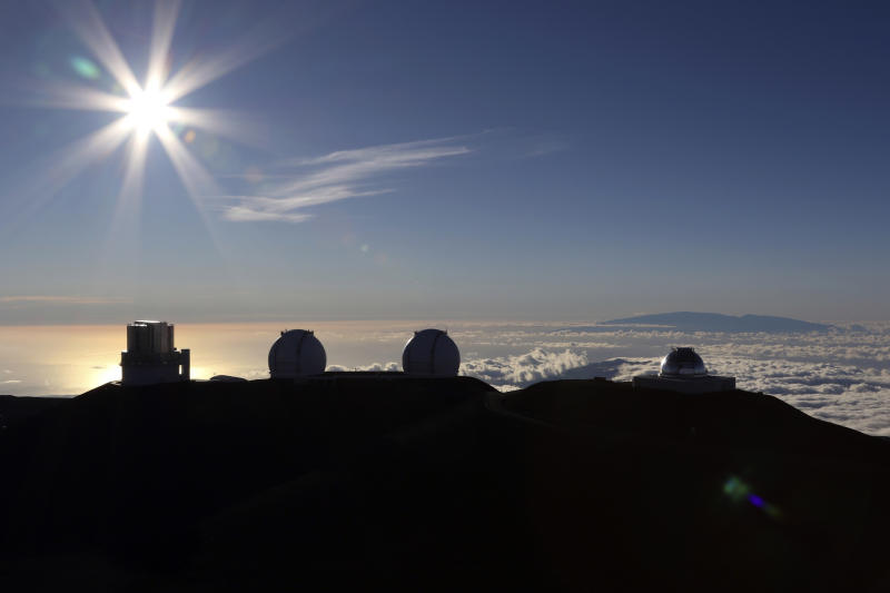 FILE - In this July 14, 2019, file photo, the sun sets behind telescopes at the summit of Mauna Kea in Hawaii. Hawaii officials are demobilizing law enforcement at a mountain where protesters are blocking construction of a giant telescope because the project isn't moving forward for now. An international consortium wants to build the Thirty Meter Telescope on Mauna Kea, Hawaii's tallest peak. But some Native Hawaiians believe the telescope will desecrate sacred land. Protesters have stopped construction from going forward since mid-July. (AP Photo/Caleb Jones, File)