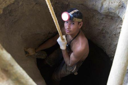 An artisanal miner uses a rudimentary pulley to descend into a hole dug at a wildcat gold mine in El Callao, Venezuela August 8, 2018. REUTERS/William Urdaneta/Files