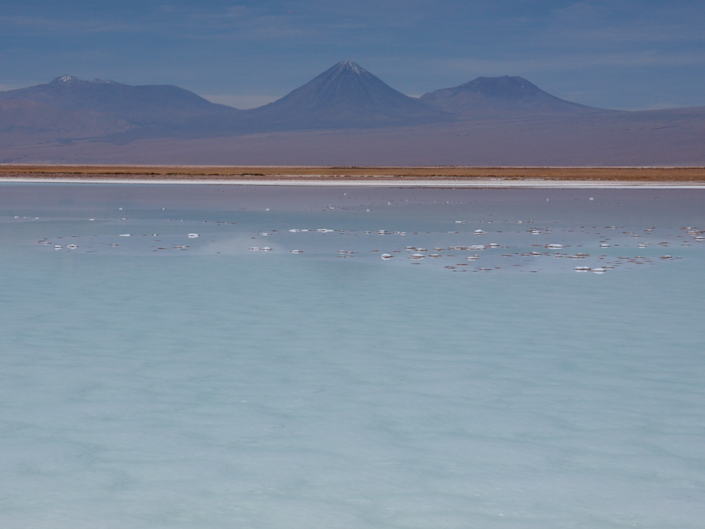 The large lake of Laguna La Brava with active volcanoes behind at sunset.