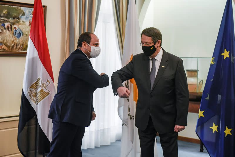 Cypru's President Nicos Anastasiades and Egypt's President Abdel Fattah al-Sisi bump their elbows before a trilateral summit between Greece, Cyprus and Egypt, at the Presidential Palace in Nicosia
