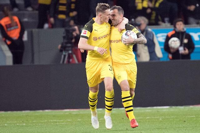 Match-winner Paco Alcacer (R) is congratulated by Danish forward Jacob Bruun Larsen (L) as Borussia Dortmund came back from two goals down to win 3-2 at Bayer Leverkusen on Saturday and knock Bayern Munich from top spot in the Bundesliga. (AFP Photo/Federico Gambarini)