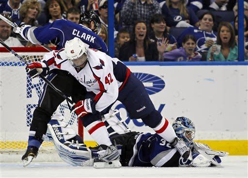 Tampa Bay Lightning goalie Mathieu Garon makes a save as Brett Clark and Washington Capitals' Joel Ward battle in front during the second period of an NHL hockey game, Saturday, Feb. 18, 2012, in Tampa, Fla. (AP Photo/Mike Carlson)