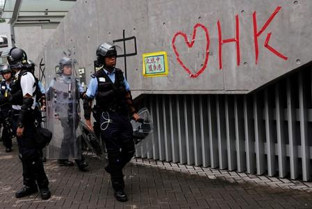 Riot police officers walk past a wall covered with messages following a day of violence over an extradition bill, in Hong Kong
