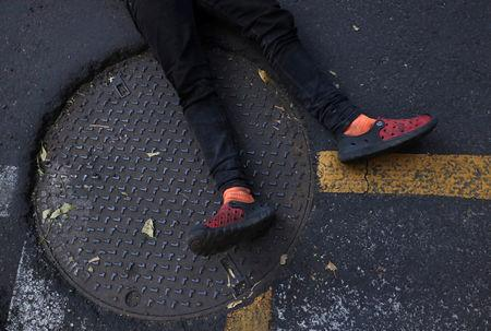 A migrant, part of a caravan traveling from Central America en route to the United States, rests on the street outside a UN Refugee Agency (UNHCR) office during a march demanding buses to take them to the U.S. border, in Mexico City