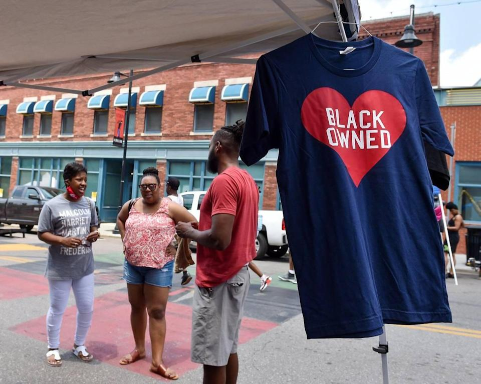Jeff Harris with Heart Black Lives, right, talks with customers during Kansas City's Juneteenth Heritage Festival in the 18th and Vine Jazz District Saturday, June 19, 2021.