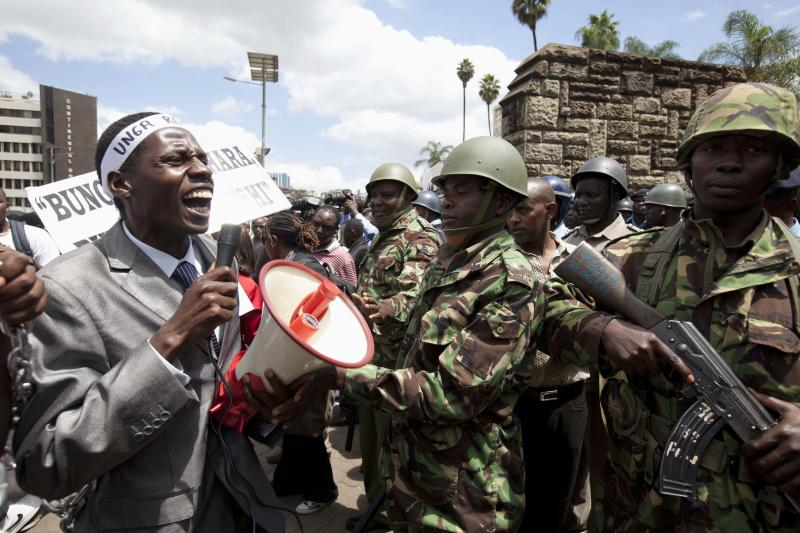 A Kenyan demonstrator is stopped by riot police near the gate of parliament in Nairobi, Kenya, Tuesday, May 14, 2013, as demonstrators marched through Nairobi city to occupy the parliament building. Police fired tear-gas, water cannons and swung their batons at protesters gathered outside Kenya's parliament building to pile pressure on the country's legislators to drop demands for a salary increment. About 250 people carrying placards and banners marched through the Nairobi's city center and staged a sit in at the entrance legislators use to enter parliament. (AP Photo/Sayyid Azim)