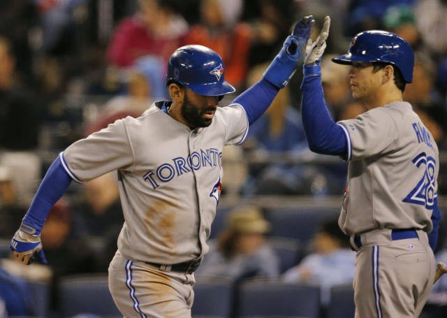 Toronto Blue Jays' Jose Bautista, left, is congratulated by on-deck batter Colby Rasmus (28) after scoring on a single by Juan Francisco during the sixth inning of a baseball game against the Kansas City Royals at Kauffman Stadium in Kansas City, Mo., Wednesday, April 30, 2014. (AP Photo/Orlin Wagner)