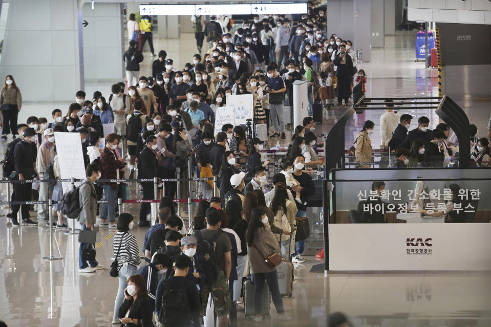 Passengers wearing face masks to help protect against the spread of the coronavirus line up to board planes ahead of the upcoming Chuseok holiday, the Korean version of Thanksgiving Day, at the domestic flight terminal of Gimpo airport in Seoul, South Korea, Wednesday, Sept. 30, 2020. (AP Photo/Ahn Young-joon)