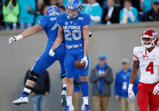 Air Force wide receiver Benjamin Waters, center, celebrates his touchdown catch with offensive lineman Parker Ferguson, left, as Fresno State defensive back Wylan Free looks on in the first half of an NCAA college football game Saturday, Oct. 12, 2019, at Air Force Academy, Colo. (AP Photo/David Zalubowski)