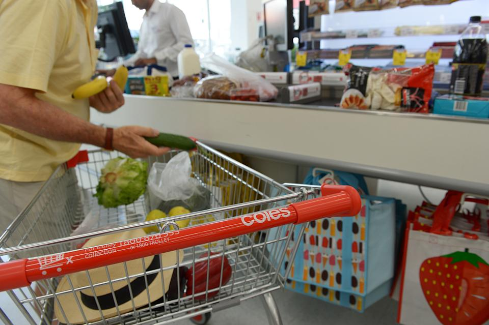 A customer unloads items from his shopping cart at a checkout counter in a Coles supermarket.