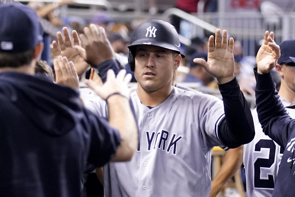New York Yankees' Anthony Rizzo is congratulated in the dugout after scoring on a wild pitch by Miami Marlins reliever Anthony Bender during the fifth inning of a baseball game, Saturday, July 31, 2021, in Miami. (AP Photo/Lynne Sladky)