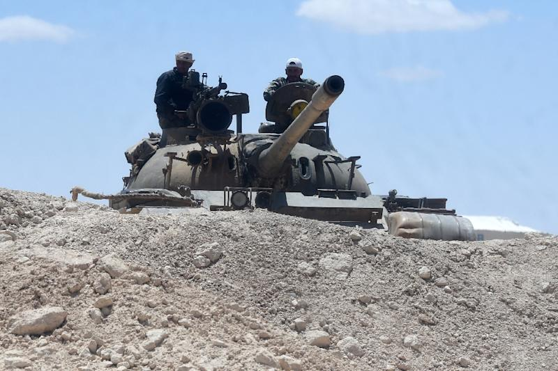 Syrian soldiers stand on a tank as they hold a position near the ancient city of Palmyra on May 5, 2016