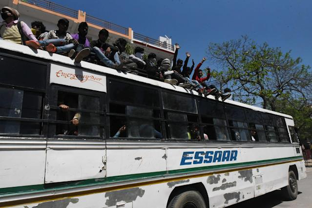\LUCKNOW, INDIA - MARCH 29: Migrant workers react from on top of a bus as they make their return home on Day 5 of the 21 day nationwide lockdown imposed by PM Narendra Modi to curb the spread of coronavirus, at Asti Road, Bakshi Ka Talab, on March 29, 2020 in Lucknow, India. (Photo by Dheeraj Dhawan/Hindustan Times via Getty Images)
