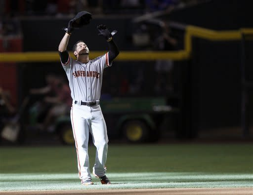 San Francisco Giants' Gregor Blanco raises his arms skyward following the playing of the National Anthem prior to the Giants' baseball game against the Arizona Diamondbacks Saturday, May 12, 2012, in Phoenix.(AP Photo/Paul Connors)