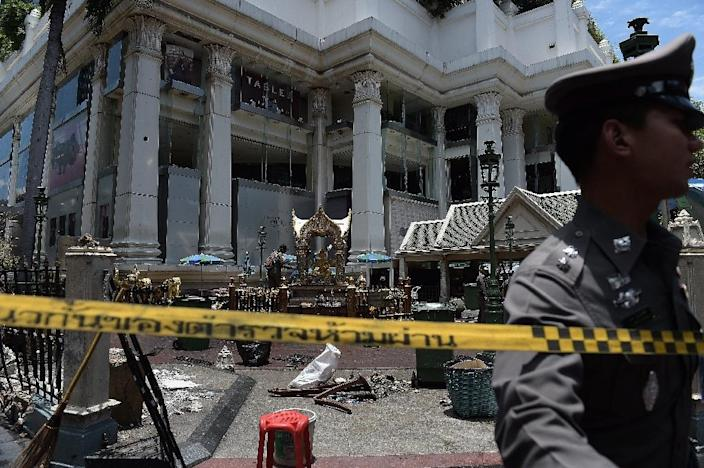 A policeman (C) inspects the cordoned-off site of a bomb blast at Bangkok's Erawan shrine on August 18, 2015 (AFP Photo/Christophe Archambault)