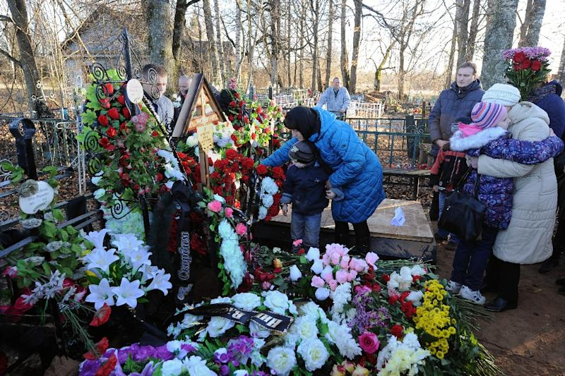 People place flowers at the grave of Nina Lushchenko, 60, a victim of the MetroJet Airbus A321 crash, during her funeral in Sitnya village in Russia's Novgorod region on November 5, 2015 (AFP Photo/Olga Maltseva)