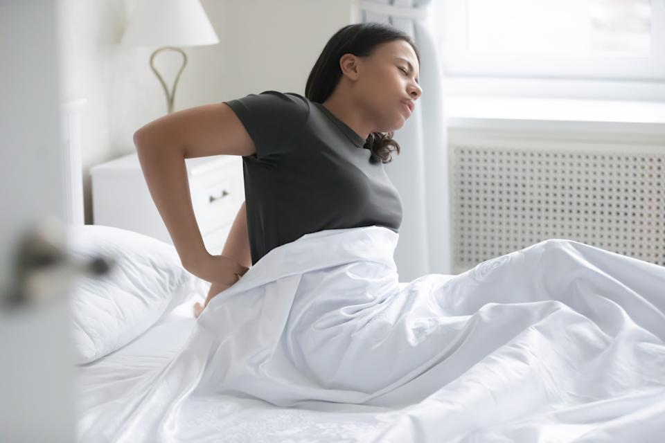 African mixed-race woman waking up sitting on bed feel low back pain after sleep caused by uncomfortable mattress, wrong position during night rest, premenstrual syndrome, violation of posture concept