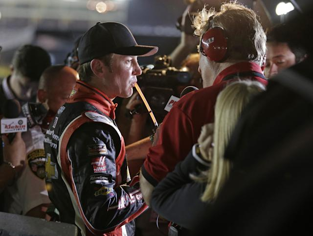 Driver Kurt Busch sips on a drink as he talks to the media after dropping out of the NASCAR Sprint Cup series Coca-Cola 600 auto race at Charlotte Motor Speedway in Concord, N.C., Sunday, May 25, 2014. (AP Photo/Chuck Burton)