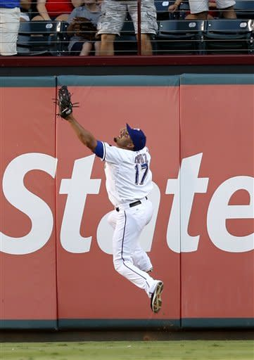Texas Rangers right fielder Nelson Cruz (17) jumps for but is unable to catch the fly ball hit by Baltimore Orioles' Nate McLouth during the first inning of a baseball game, Monday, Aug. 20, 2012, in Arlington, Texas. (AP Photo/Jim Cowsert)