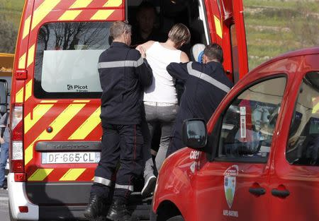 French firefighters evacuate a woman near the Tocqueville high school after a shooting incident injuring at least eight people, in Grasse, southern France, March 16, 2017.   REUTERS/Eric Gaillard