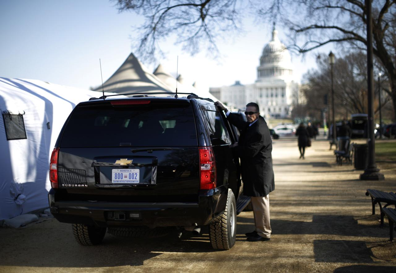 """U.S. President Barack Obama's SUV is guarded by a Secret Service agent as Obama (not pictured) meets with people who are fasting for immigration reform in their tent (L) on the Washingon Mall, November 29, 2013. Since November 12, immigration advocates comprising """"Fast for Families"""" have abstained from food as they call on congress to take up action on the immigration issue. REUTERS/Jason Reed (UNITED STATES - Tags: POLITICS CIVIL UNREST SOCIETY IMMIGRATION)"""