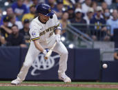 Milwaukee Brewers starting pitcher Eric Lauer bunts for a base hit against the Pittsburgh Pirates during the third inning of a baseball game Monday, Aug. 2, 2021, in Milwaukee. (AP Photo/Jeffrey Phelps)