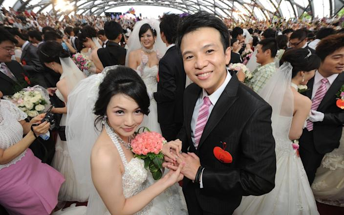 A couple - not those in the story - poses for photos during a mass wedding ceremony organized by Taipei city government in 2010 - SAM YEH /AFP