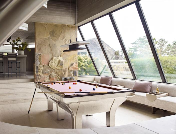 "<div class=""caption""> To complement the metal pool table, which came with the house, Moon commissioned a suspended lamp in darkened brass and marble from <a href=""https://www.liaigre.com/en/"" rel=""nofollow noopener"" target=""_blank"" data-ylk=""slk:Liaigre"" class=""link rapid-noclick-resp"">Liaigre</a>, and designed a built-in banquette with leather armrests and cerused oak wooden trays. </div>"