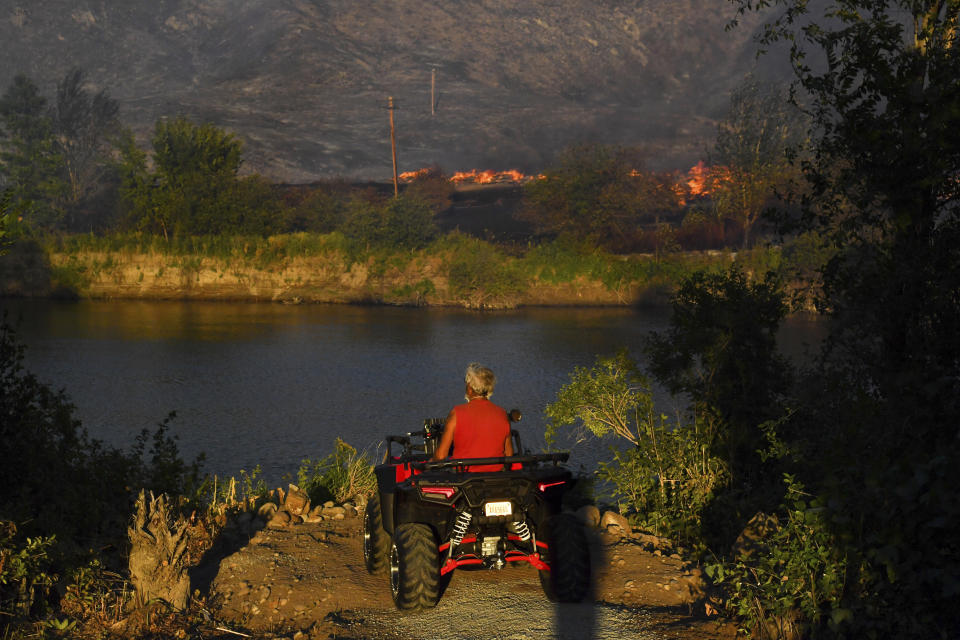 A man pauses his ATV on the banks of the Okanogan River and watches a pile of old railroad ties burn on Monday, September 7, 2020, in Okanogan. Source: AP