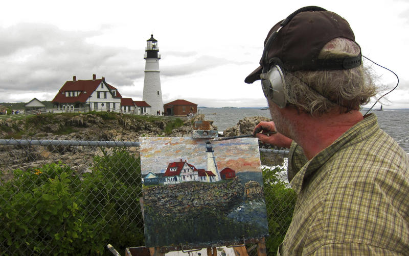 An artist works on his rendition of the Portland Head Light in Cape Elizabeth, Maine August 10, 2011. The lighthouse became an iconic subject after being painted by artist Edward Hopper in 1927. REUTERS/Kevin Lamarque (UNITED STATES - Tags: SOCIETY)