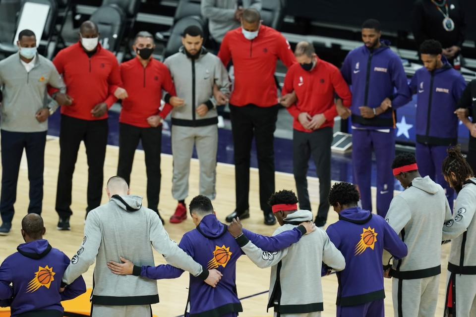Members of the Phoenix Suns and the Toronto Raptors form a circle during the American national anthem prior to an NBA basketball game Wednesday, Jan. 6, 2021, in Phoenix. (AP Photo/Ross D. Franklin)