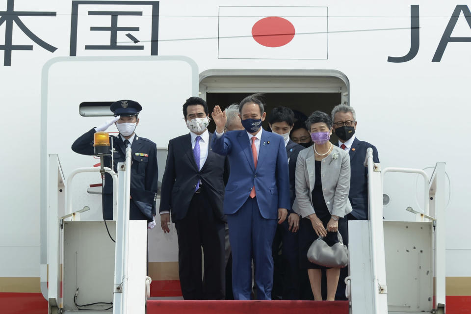 In this photo released by Indonesian Presidential Palace, Japanese Prime Minister Yoshihide Suga, center, waves, accompanied by his wife Mariko Suga, left in foreground, upon arrival at Halim Perdanakusuma Airport in Jakarta, Indonesia, Tuesday, Oct. 20, 2020. Suga arrived in Indonesia on the second leg of his first overseas trip as premier to underscore his government's aims of countering China in the region (Indonesian Presidential Palace via AP)