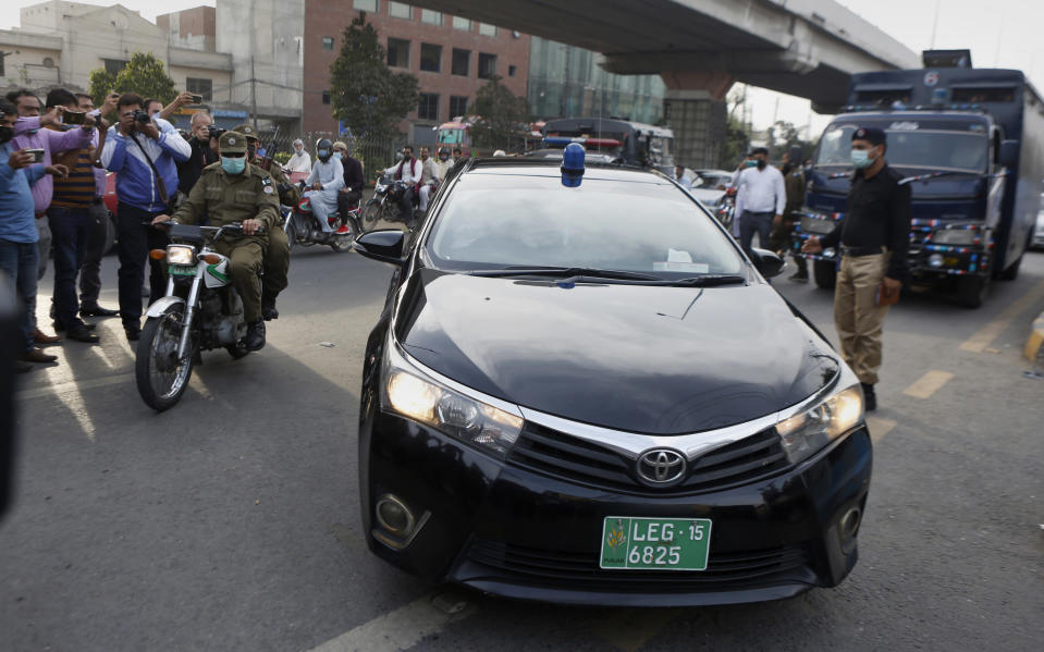 Members of media film a car carrying an anti-terrorism court judge Arshad Hussain Butta arriving at district jail, where the special court setup for the trial of prime suspects in motorway gang-rape case, in Lahore, Pakistan, Saturday, March 20, 2021. A prosecutor says an anti-terrorism court in Pakistan has awarded death penalty and 14 year jail terms to two men held for motorway gang rape of a woman in front of her children last year in eastern Punjab province. (AP Photo/K.M. Chaudary)