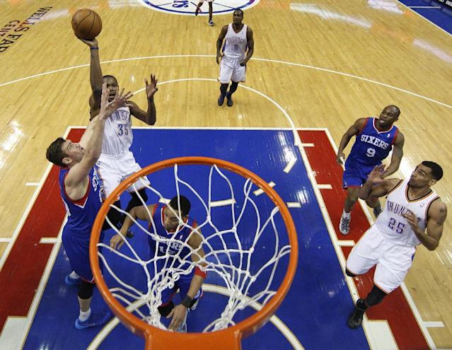 Oklahoma City Thunder's Kevin Durant puts up a shot with Philadelphia 76ers' Spencer Hawes, left, defending during the first half of an NBA basketball game, Saturday, Jan. 25, 2014, in Philadelphia. (AP Photo/Chris Szagola)