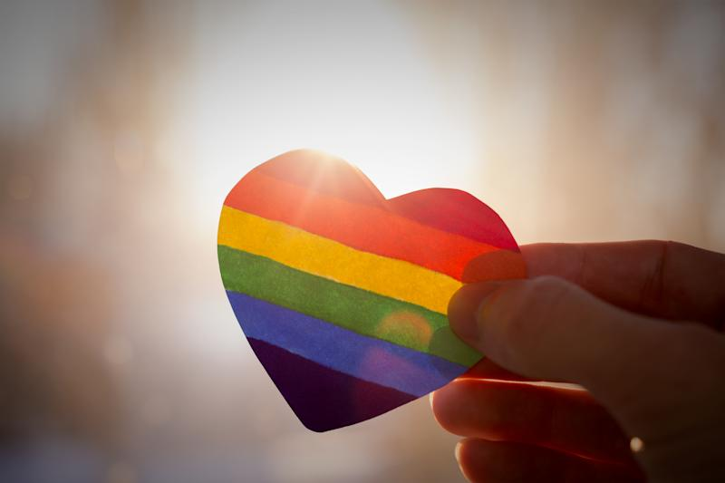 A heart shaped rainbow flag silhouetted against the sun. The rainbow flag, commonly known as the gay pride flag or LGBTQ pride flag, is a symbol of lesbian, gay, bisexual, transgender, and queer pride and LGBTQ social movements. (Photo: Getty)