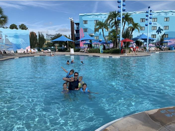 The author and his four children swimming in a relatively empty swimming pool at Disney's Art of Animation resort