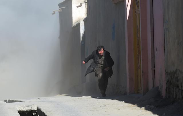 <p>An Afghan man runs away as dust blows in the aftermath of the third blast at a Shiite cultural centre in Kabul on Dec. 28, 2017. (Photo: Shah Marai/AFP/Getty Images) </p>