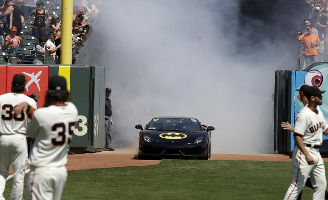 The Batmobile drives into AT&T Park with Miles Scott, dressed as Batkid, who threw out the ceremonial first pitch before the home opener MLB baseball game between the San Francisco Giants and the Arizona Diamondbacks in San Francisco, Tuesday, April 8, 2014. On Nov. 15, 2013, Scott, a Northern California boy with leukemia, fought villains and rescued a damsel in distress as a caped crusader through The Greater Bay Area Make-A-Wish Foundation. (AP Photo/Eric Risberg, Pool)