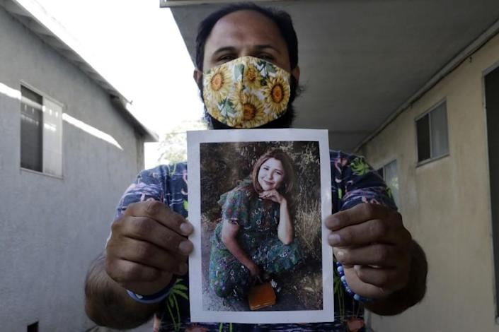 "Albert Corado holds a photo of his sister, Melyda, who was fatally shot by an LAPD officer in 2018 at the Trader Joe's in Silver Lake. <span class=""copyright"">(Myung J. Chun/Los Angeles Times)</span>"