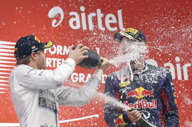 Mercedes Formula One driver Nico Rosberg of Germany (L) sprays champagne on the face of Red Bull Formula One driver Sebastian Vettel of Germany on the podium after the Indian F1 Grand Prix at the Buddh International Circuit in Greater Noida, on the outskirts of New Delhi, October 27, 2013. Vettel became Formula One's youngest four-times world champion on Sunday after winning the Indian Grand Prix for Red Bull. REUTERS/Ahmad Masood (INDIA - Tags: SPORT MOTORSPORT F1)