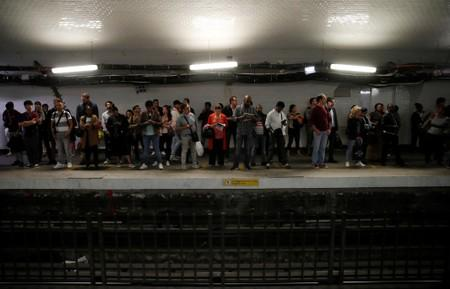 Commuters wait to board a metro at the Gare du Nord subway station during a strike by all unions of the Paris transport network (RATP) against pension reform plans in Paris