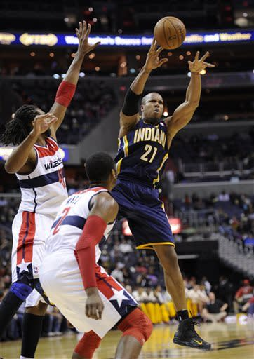 Indiana Pacers forward David West (21) passes the ball against Washington Wizards center Nene, left, and John Wall, center, during the first half of an NBA basketball game, Saturday, April 6, 2013, in Washington. (AP Photo/Nick Wass)