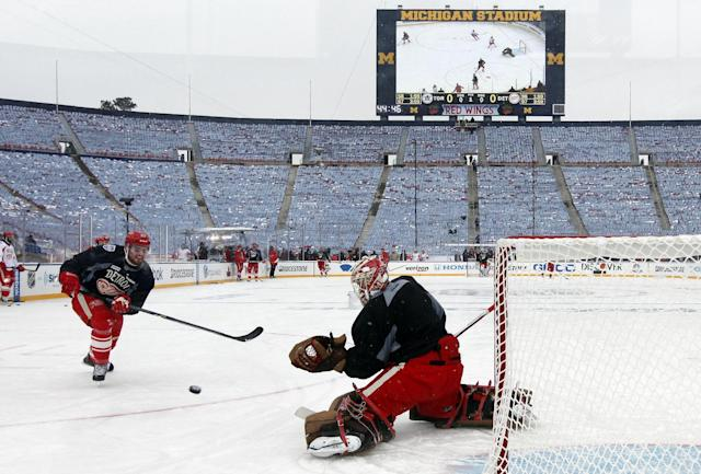 Detroit Red Wings defenseman Brian Lashoff (23) shoots on goalie Jimmy Howard (35) during practice on the outdoor rink for the NHL Winter Classic hockey game against the Toronto Maple Leafs at Michigan Stadium in Ann Arbor, Mich., Tuesday, Dec. 31, 2013. The game is scheduled for New Year's Day. (AP Photo/Paul Sancya)