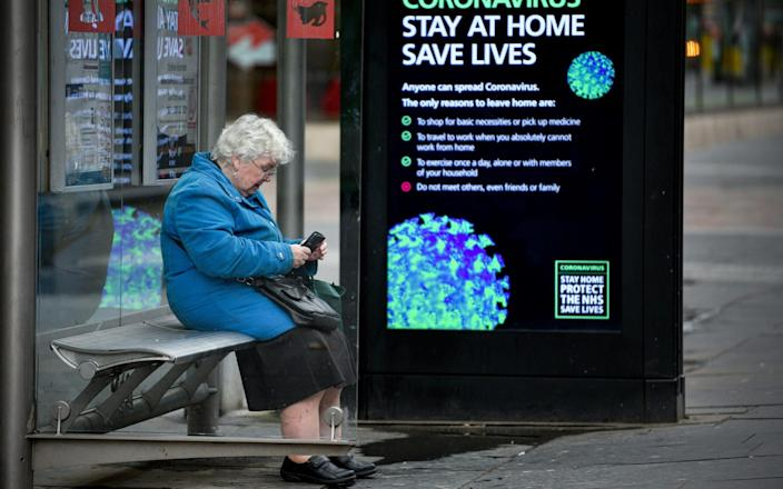 An elderly woman sits in a bus stop on Argyll Street as people are asked to socially distance themselves amid the coronavirus outbreak on March 25, 2020 in Glasgow - Jeff J Mitchell/Getty