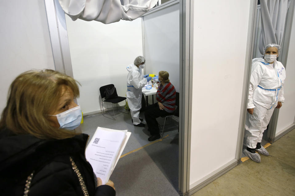 A medical worker gives a shot of Chinese Sinopharm COVID-19 vaccine to a woman during the vaccination in Belgrade, Serbia, Wednesday, Feb. 17, 2021. Serbian health expert Chief epidemiologist Predrag Kon on Tuesday March 2, 2021, called for the government to introduce a state of emergency and a strict lockdown to halt a surge in coronavirus infections in the Balkan country. (AP Photo/Darko Vojinovic)