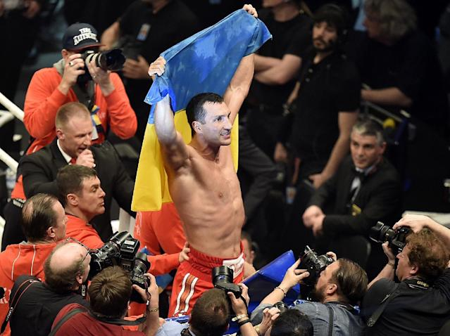 World boxing champion Wladimir Klitschko celebrates with the Ukrainian flag after defeating Samoan-born Australian challenger Alex Leapai following their IBF, IBO, WBO and WBA heavyweight title bout in Oberhausen, Germany, Saturday, April 26, 2014. Klitschko won the fight by technical knock out in the fifth round. (AP Photo/Martin Meissner)