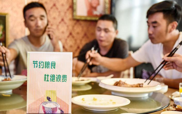 Diners are being encouraged to limit how much they order in restaurants - STR/AFP
