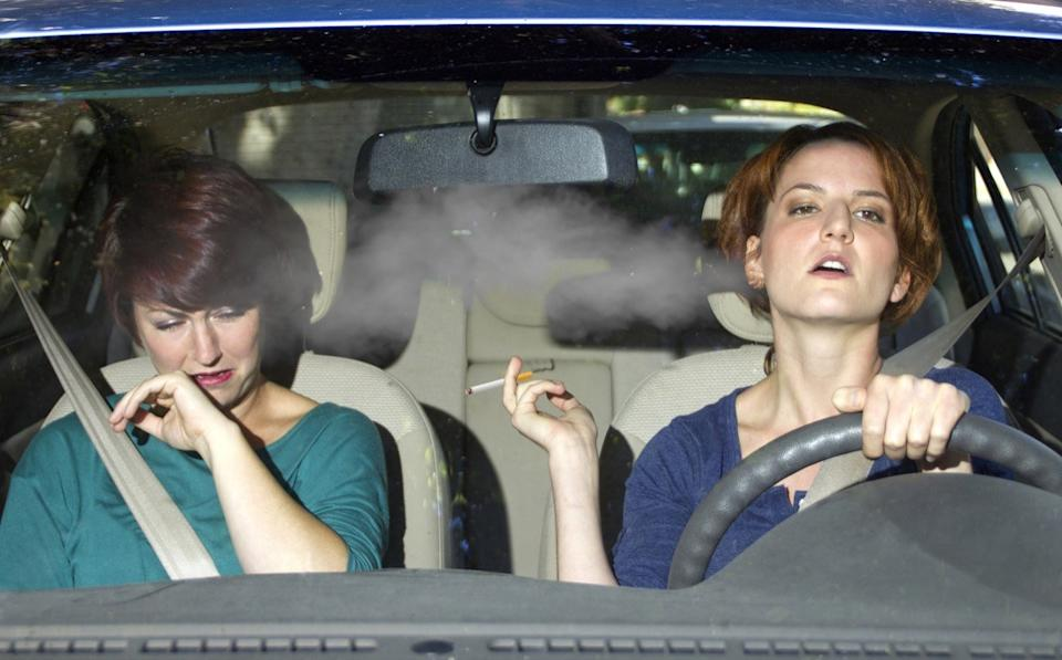 female smoking while driving inside the car